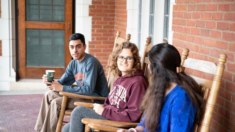 Students sitting on the porch at Hillcrest Hall